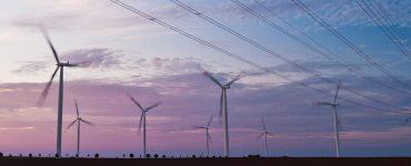Windkraftturbinen und Ueberlandleitungen im Morgenlicht